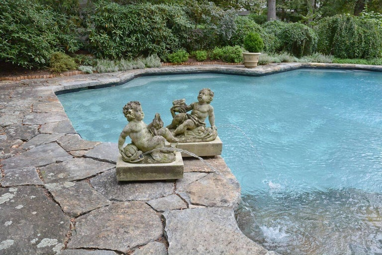 A pair of carved Vicenza stone fountainheads, each with curly haired cherub reclining on dolphin, one fountainhead piped in two places, the other piped in one, on rectangular bases, Italian, circa 1920. Measure: 28 ins high including base, bases 25