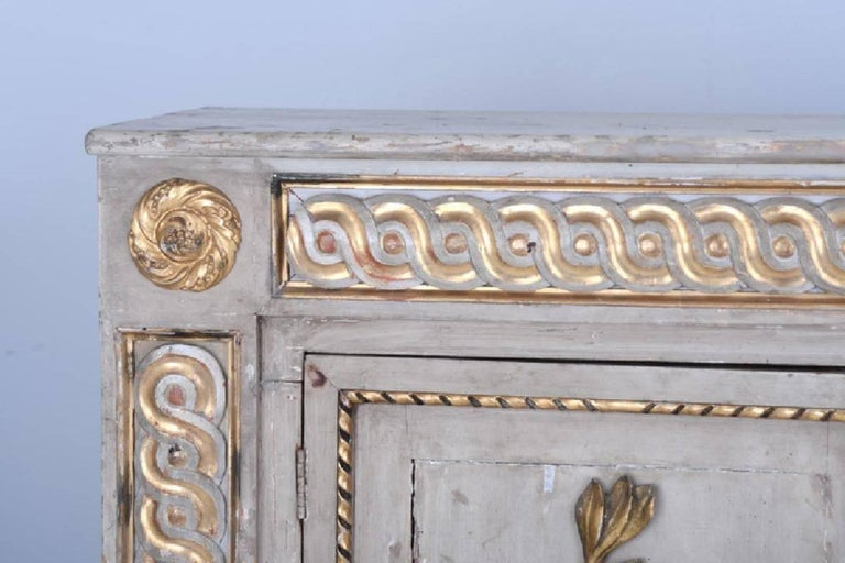 Period 18th century neoclassical sideboard cabinet - Exquisitely executed - Great narrow depth - Three cabinet doors of naturally carved wooden laurel and oak leaves in original gilt - Gilded guilloche.