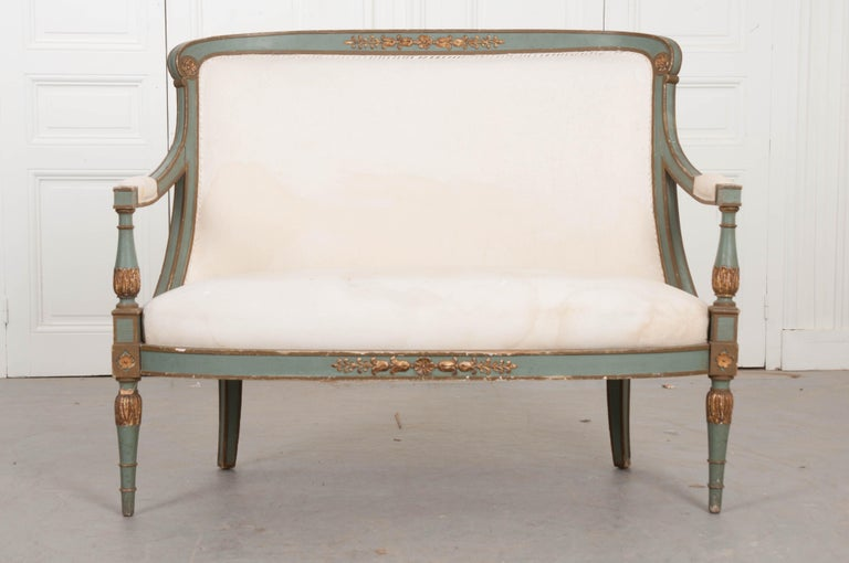 An empirically styled settee from 19th century, France. The small sofa has a frame that is finished in an exceptional painted jade or turquoise and gold parcel-gilt. It is upholstered in a temporary canvas fabric that is stapled to the frame for