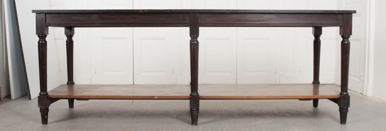 A gripping pair of dark drapery tables from 1900s France. The long tables both have tops that are painted black, slightly darker than the dark brown stain used to color the apron and legs. There is an undertier shelf that runs the length of each