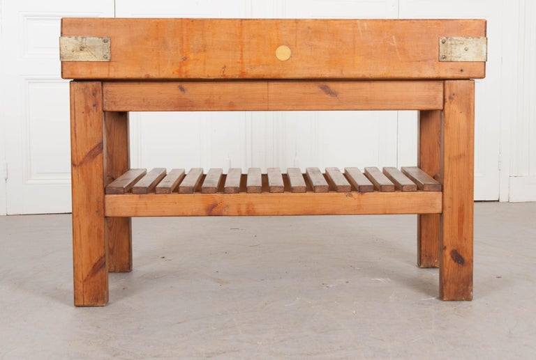 A substantial pine butcher block, from 20th century, France. The table's top is made from thick pine blocks that have been tightly joined together and bound with steel bindings. The work surface has acquired some patination from years of knife and