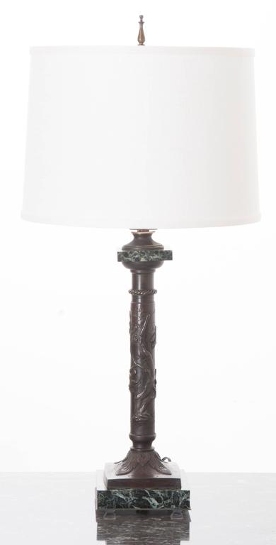 This small, decorative table lamp has been fashioned using an ornate bronze column that rests on a square marble base. The column's shaft features a gnarly tree with sparrows circling in pursuit of its precious fruit. The column's base is decorated