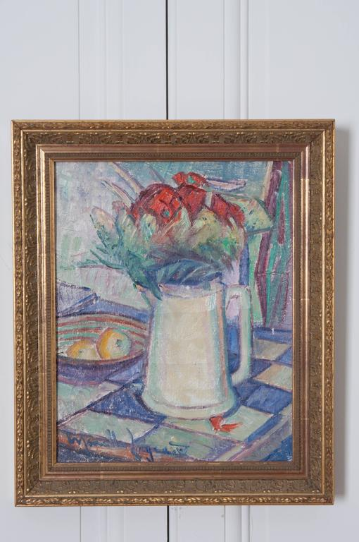 A colorful antique oil painting from the end of the 19th century, France. The work exhibits a pitcher on a checkered counter or tabletop, full of flowers. A bowl containing fruit is at its side. The piece is set in a remarkable gold gilt frame that