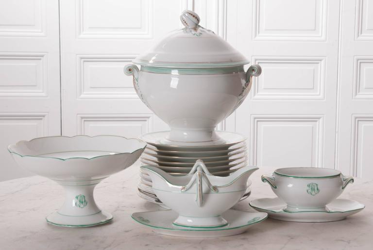 A beautiful set of old Pairs porcelain dinner pieces from mid-19th century France. The service pieces are monogrammed and trimmed in a lovely blue-green and gold. The soup tureen has styled handles with foliate details and a lid with a pumpkin