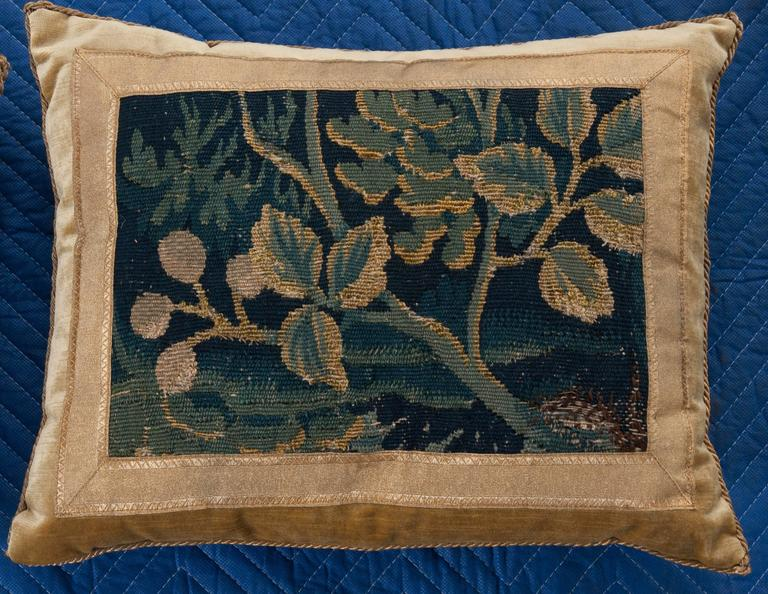 17th century Verdure tapestry fragment framed with vintage gold metallic gallon on pale straw velvet. Hand trimmed with vintage gold metallic cording knotted in the corners. Down filled. Available for individual sale: $2095.00 each.
