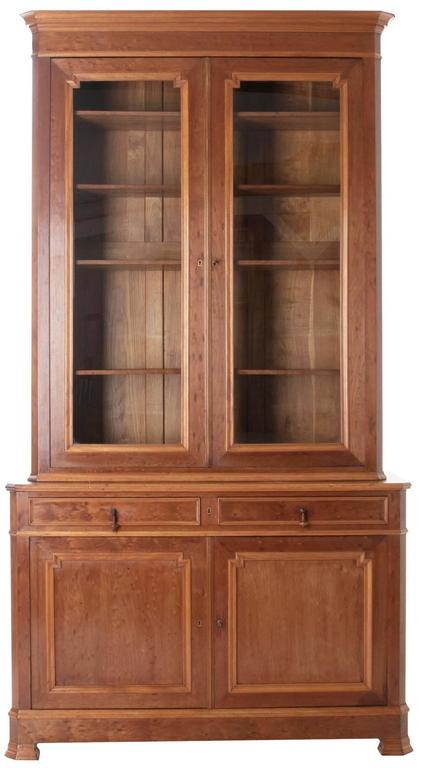French Louis Philippe bibliotheque in bird's-eye mahogany. Wonderful crown over bibliotheque of two glass locking doors over its buffet of two drawers and two doors. Four adjustable shelves in top and one fitted shelf in bottom, behind closed doors.