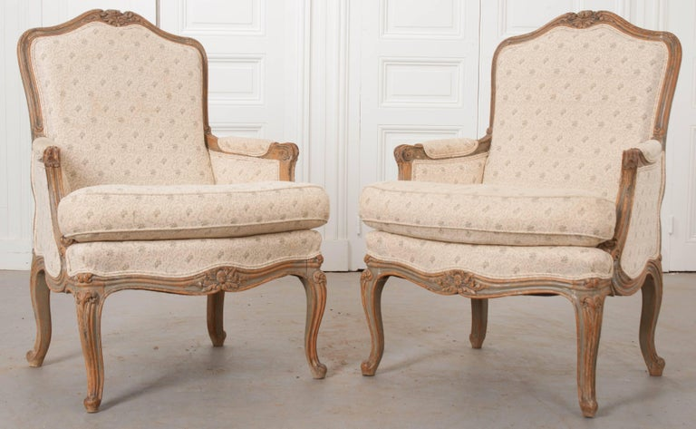A fabulous pair of carved and painted Louis XV style bergères from 19th century France. These beautiful chairs are upholstered in a patterned linen and have a soft green plaid upholstered posterior. The upholstery is not original to the pair, and
