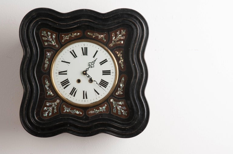 A Napoleon III style wall clock, with exceptional mother-of-pearl inlay, from 1850s France. This shapely clock is square in shape, with a wonderfully wavy frame. This frame is hand-carved and ebonized. It closes before a hand-painted clock face,