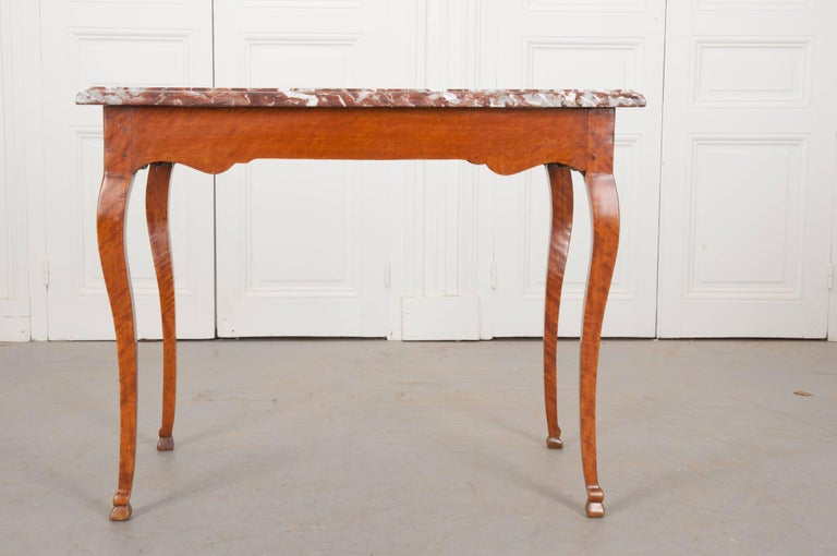A breathtaking birch writing table, made at the beginning if the 19th century in France. The marble top is a rich cinnamon color, with vibrant flashed of white throughout, and a wonderful finished edge. The base is made of solid birch with beautiful