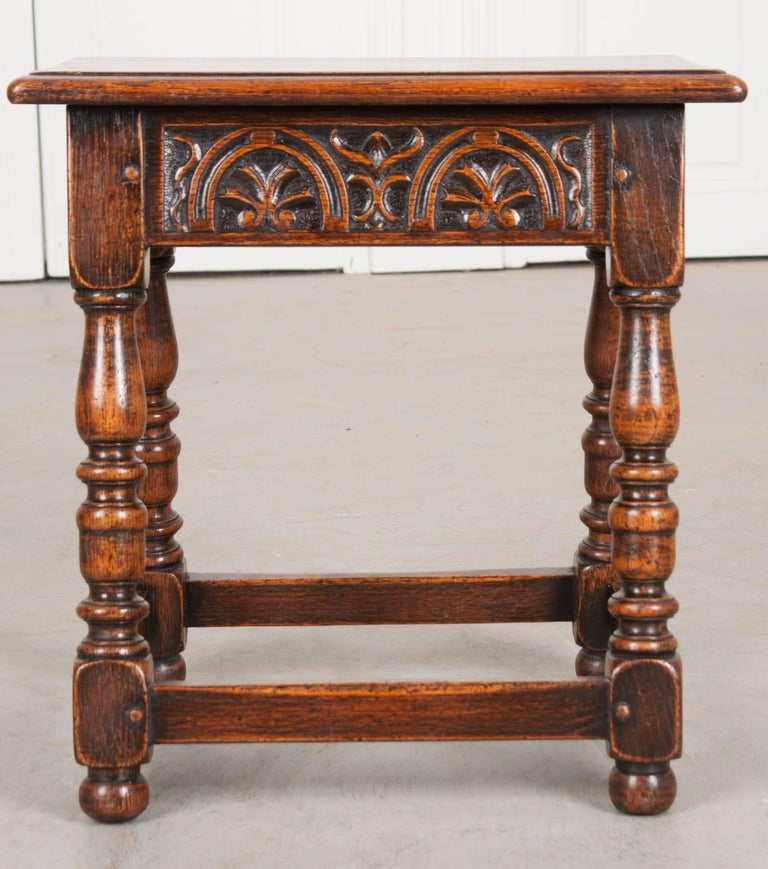 A fantastic little oak stool, carved by hand in England, circa 1890. The apron is particularly special with this antique in that it is wonderfully carved, with symmetrical arched horseshoes on all sides. The legs are beautifully turned in a