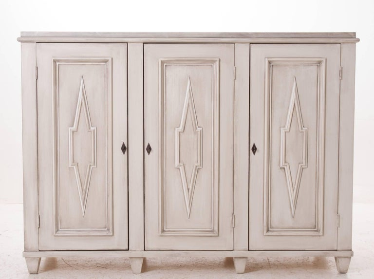 A fabulous example of a Swedish Gustavian buffet sideboard. This buffet has an impressive faux white marble top with a cream and gray wash for the base. Handcrafted paneling and designs give this buffet the look and the depth you will need for your