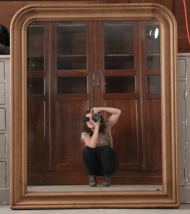 A fantastic 19th century Louis Philippe mirror, which contains its original mercury glass that is framed in a bleached oak surround. The moulded oak surround has been carved into the classic Louis Philippe shape. The mercury glass is original to the