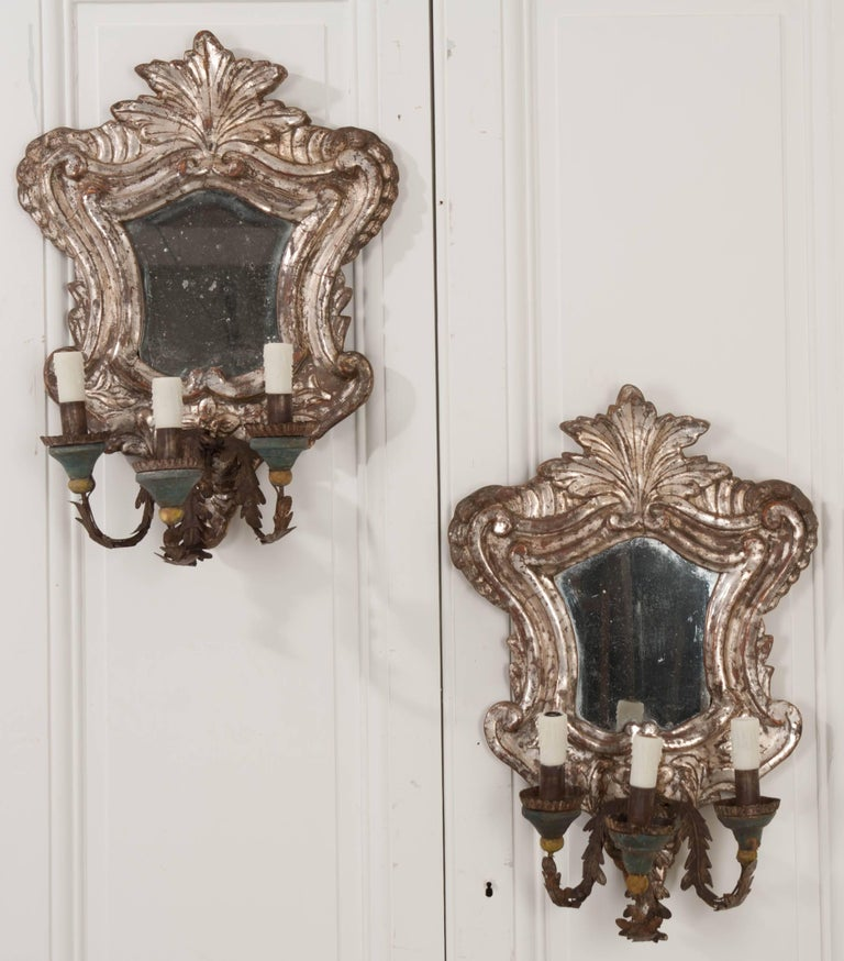 An elegant pair of silver gilt three-light sconces from Italy, circa 1780. These beautifully carved sconces have been made in the Rococo style, with beautiful silver gilt that is still largely intact. The pair contain shaped mirrors, that, along