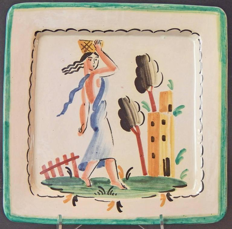Painted with freshness and sophistication, this pair of Italian Art Deco plates depict elegant female figures, each balancing baskets on their heads, striding toward a tower in the distance.  One in a blue Classical robe, with her Art Deco hair