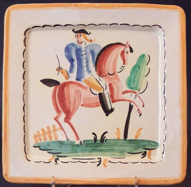 Painted with freshness and sophistication, this pair of Italian Art Deco plates depict elegant, stylized horses, one ridden by a blue-coated man in a bicorn hat and another pair standing regally by a fence and tree. The palette -- ocean blue,