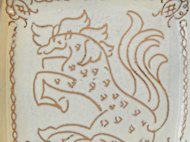 A large, early and rare example of Glidden Parker's ceramic artistry, this striking tray depicting a horse with flying tail and mane depicts his mastery of the sgraffito technique, whereby the artist created a design by scraping through the wet