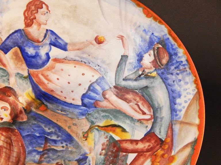 Whimsical and vividly glazed, this fabulous, unique Art Deco bowl depicts two contrasting scenes from a rural seaside village: a father and son fishing at the shore, and a young woman and man, the former offering a piece of fruit to the latter like