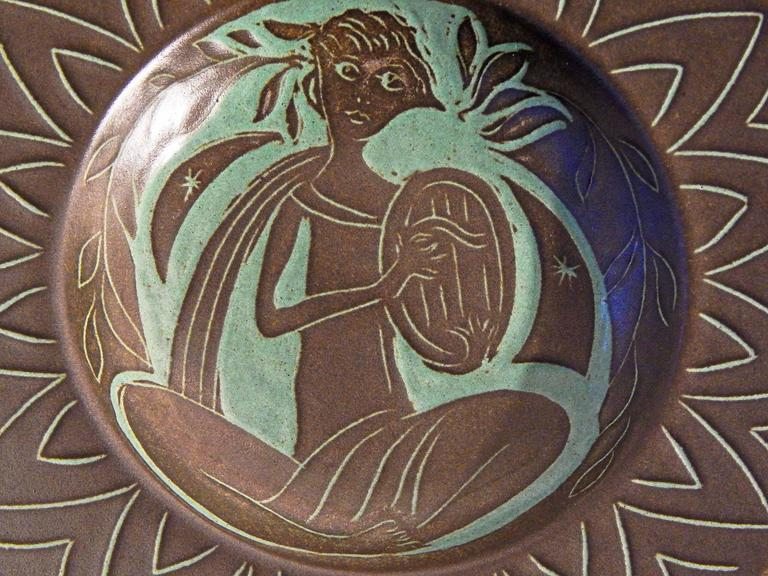This very fine and highly rare bowl, featuring a seated female figure in classical robes who is plucking an oval harp, exhibits the incised design and rich colors that Rudolf Petersen is known for. The artist worked in Rødovre, Denmark from the