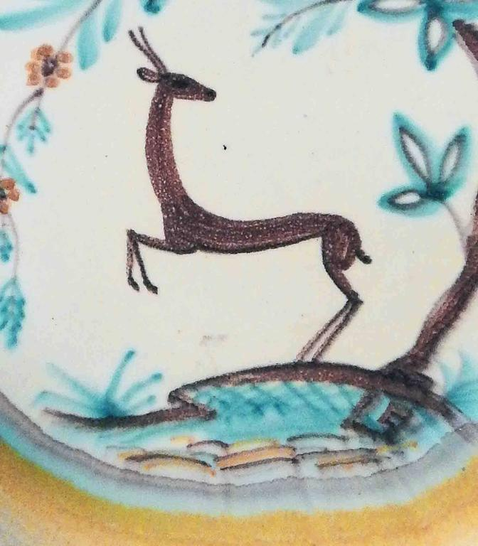 Beautifully glazed in sky blues and golden yellows, this large, low Art Deco bowl features a rearing deer highly stylized in the manner of the period below an arching tree with oversized foliage. This piece was created in Finland, probably in the
