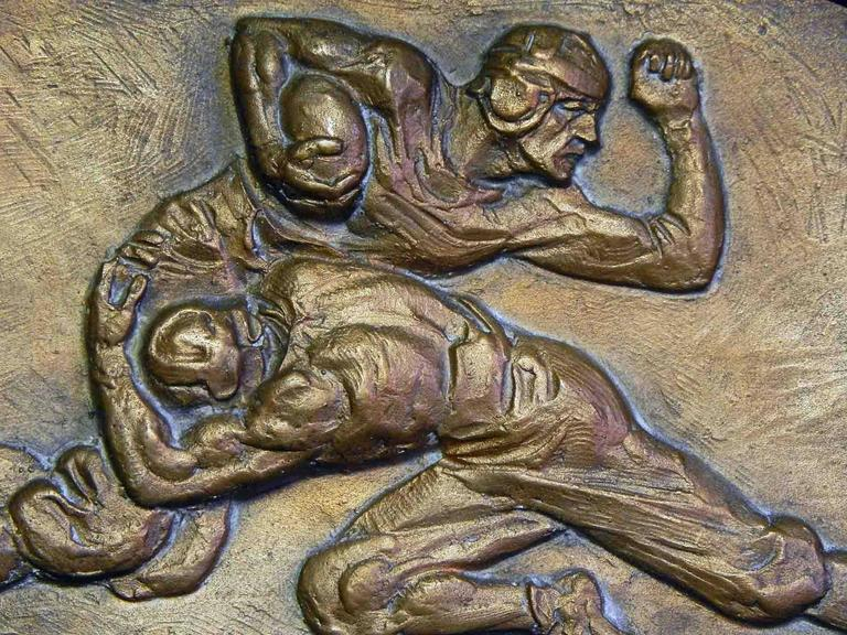Sculpted and cast as the prototype for a bronze awards plaque celebrating accomplishment in American football, this piece shows two players in the middle of a dramatic tackle. The artist, Fred Torrey, is best known for his