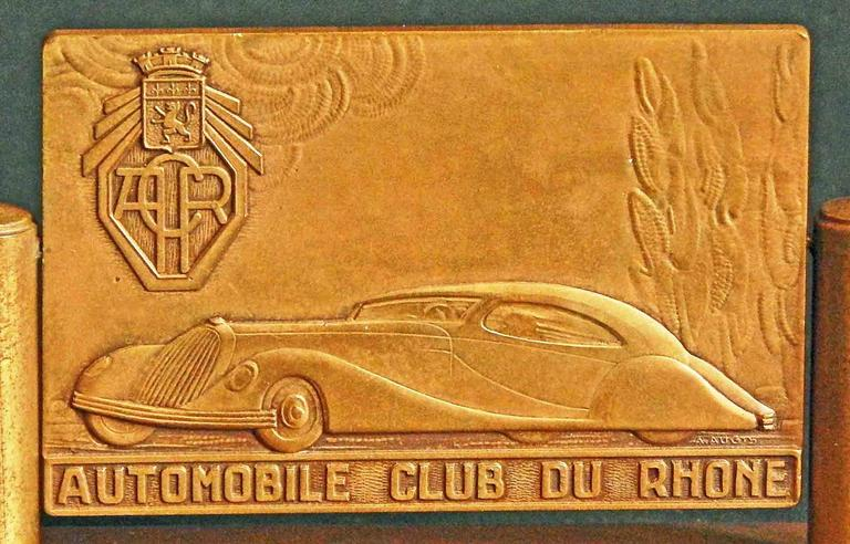 This rare and striking desk accessory, consisting of a bas relief sculptural bronze plaque suspended above a bronze base, was sculpted by A. Augis for the Automobile Club of Rhone, and depicts a streamlined luxury car -- probably a Talbot-Lago coupe