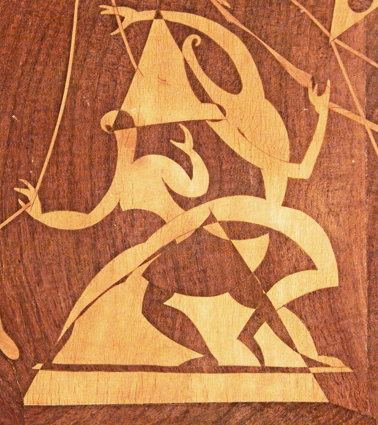 Brilliantly designed and executed, this example of wood inlay Folk Art, by Renato Maggiora in 1953, depicts a pair of circus acrobats at the centre, highly stylized and showing the influence of Cubism, Surrealism and midcentury abstraction. To the