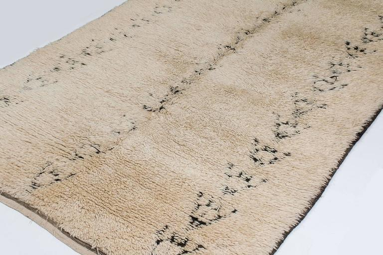 This vintage Beni Alaham carpet is woven in a fine, dense wool with an exceptional patina and silky hand. Knotted in a charcoal black wool on an ivory ground. This is a Moroccan carpet is calm and minimal.   This rug has a half-hidden relief design,