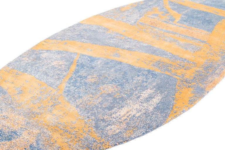 A collaboration between creative minds Joseph Carini and Karl Klingbiel, tractor trailer is a boldly captivating design. This oval shaped rug has an icy blue field which is broken up with yellow brushstrokes. This contemporary design is painterly,