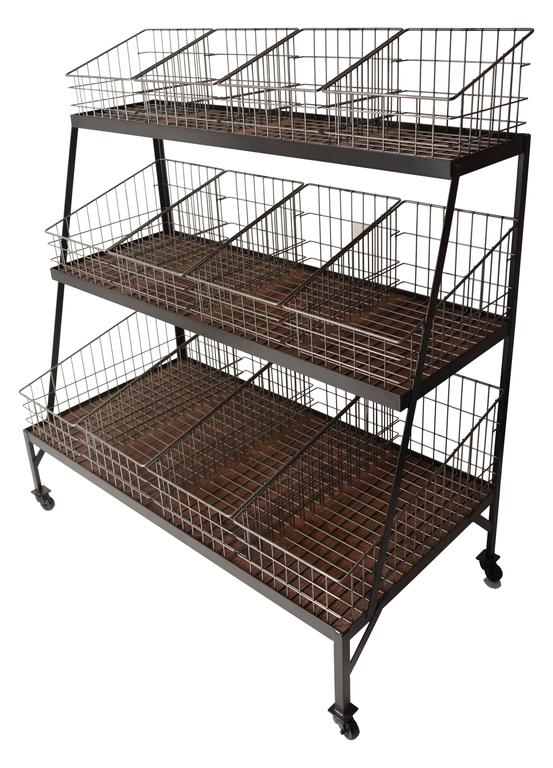 Three-tiered steel frame on steel casters. Each level contains four removable wire-framed baskets on a wooden shelf. This piece was inspired by an original mercantile display unit found in Nashville, Tennessee that dates from the 1920s. Please