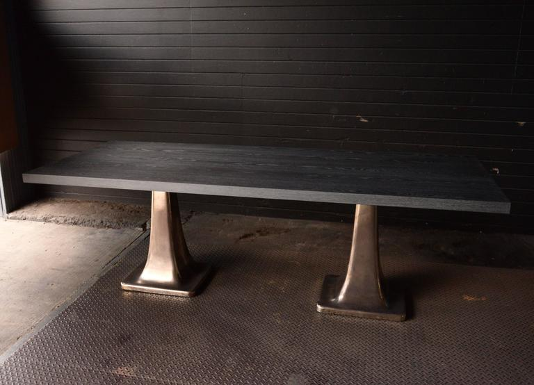 Rectangular cerused gray oak top dining table with two cast bronze pedestal bases patterned from a turn of the century machine shop lathe stand.  Custom sizes welcomed.