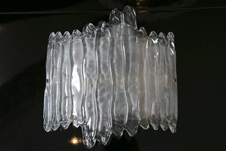 A dramatic and shimmery pair of curved wall lights blown to appear as melting icicles, illuminated with 2 candelabra base sockets for up to 60 watts each