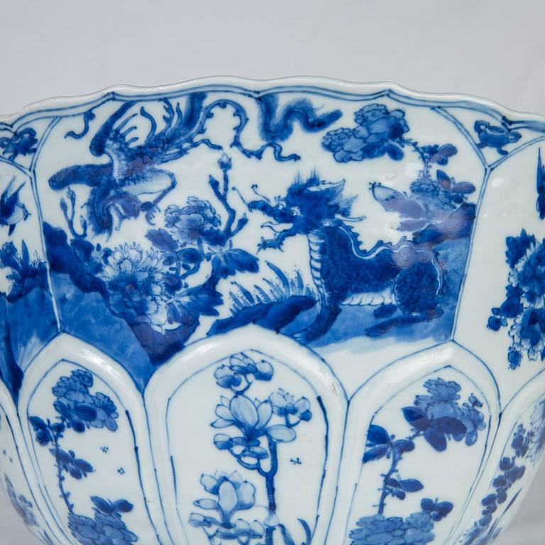 A large Kangxi porcelain Blue and White punch bowl hand-painted in underglaze cobalt blue (China, circa 1700). The outside of the bowl is divided into six panels. Each panel is well painted with a unique and lively scene. Each scene is painted in
