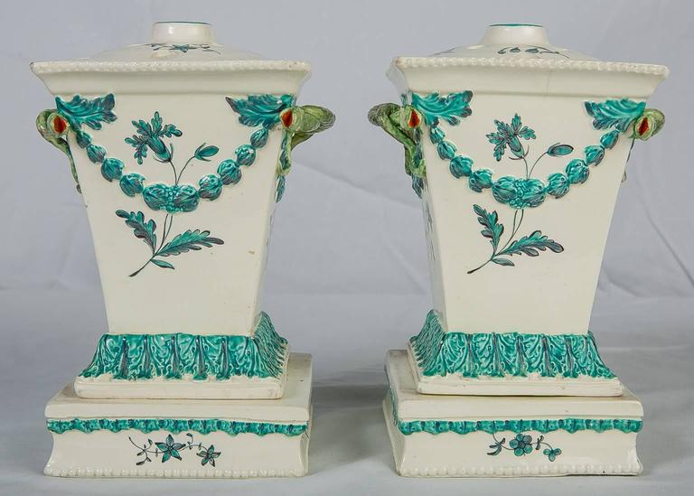 A pair of 18th century creamware flower holders made in England by Neale & Co. Neale & Co. was one of the finest 18th century English potteries. The flower holders are decorated with turquoise swags and delicately painted flowers. The tops are