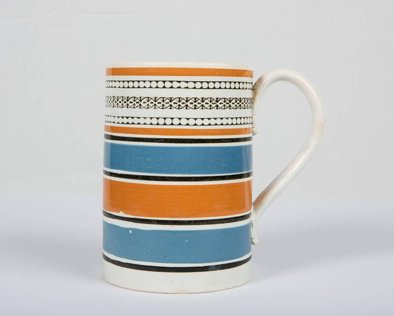 A handsome antique Mochaware quart mug or tankard that is wider at the bottom and slightly tapers as it goes up. Made in England, circa 1820, this mug was decorated with slip in broad machine-turned bands of orange and blue. The top of the tankard