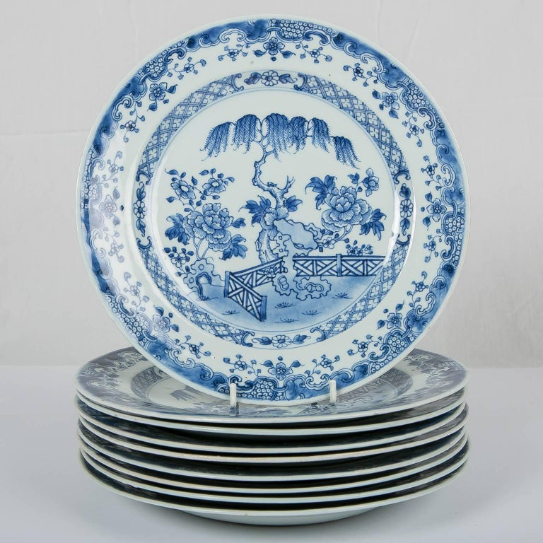A set of ten 18th century Chinese blue and white dishes made during the reign of the Qianlong Emperor (1736-1795). Hand-painted in light cobalt blue the centre of each plate shows a view of a scholar's garden featuring a garden fence, Taihu rocks,