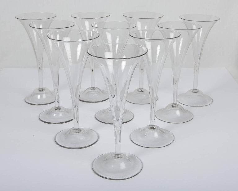 A wonderful set of ten English clear white champagne glasses, the funnel shaped bowls set upon a tubular stem rising from a circular foot. At the center on the bottom of the foot is a pontil mark (see images). The mark is the scar where the pontil