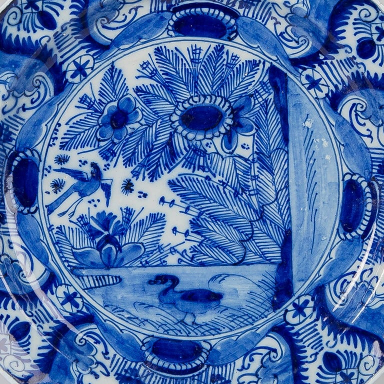 A Dutch Delft 10 inch charger where the center shows a beautiful, lively, and very detailed ducks-in-a-pond scene with giant flowers overhanging the edge of the pond, a duck swimming, and a long-tailed bird flying above. The scene and the