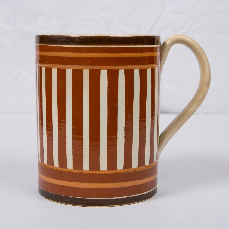 This antique creamware mochaware mug or tankard is slip decorated with both vertical and horizontal stripes in three shades of brown. No two mochaware pieces are the same. Each potter made his own choices in color and design. What makes this mug so