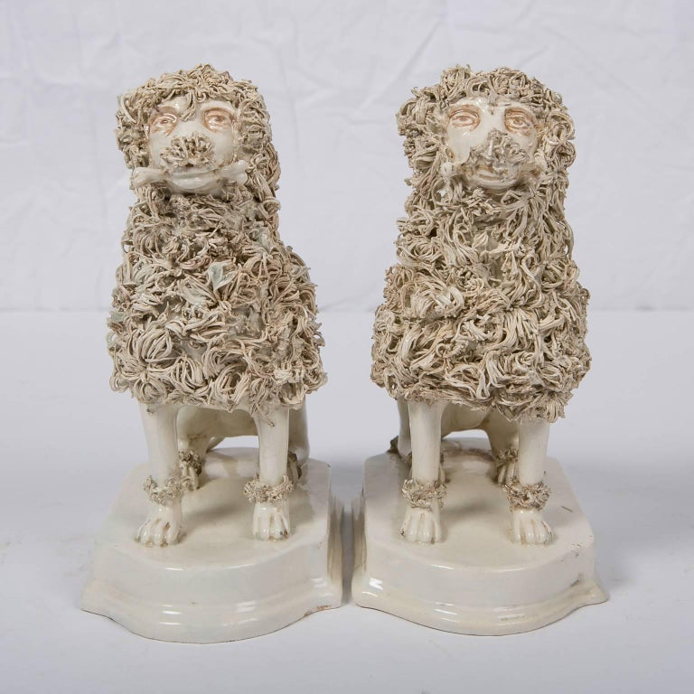 We are pleased to offer this pair of wonderful Antique Creamware Dogs Made by Nove di Bassano. These creamware poodles were made in Italy in the first quarter of the 19th century. Each is modelled seated, on a stepped base. The technique for making