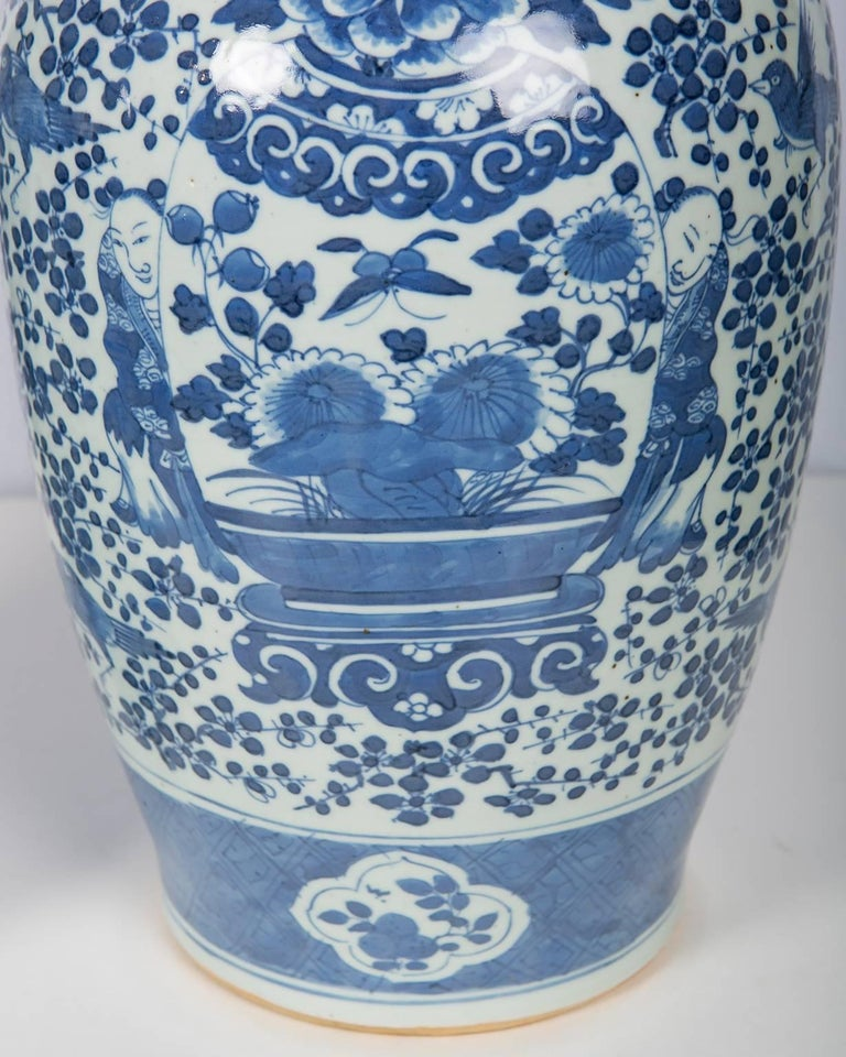 A pair of large antique Chinese blue and white covered jars painted in a soft shade of blue. Each jar is decorated with flowers, a butterfly. The most interesting aspect of the vases is a scene with two young boys peeking out from behind a large