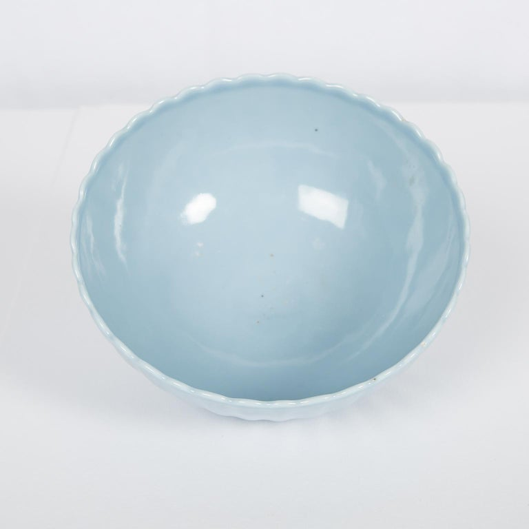 The soft color of this Chinese clair de lune chrysanthemum bowl comes from the glazing technique, which employed a glaze with a small cobalt content to achieve the pale blue hue. The Chinese call this hue of blue, tian lan you,