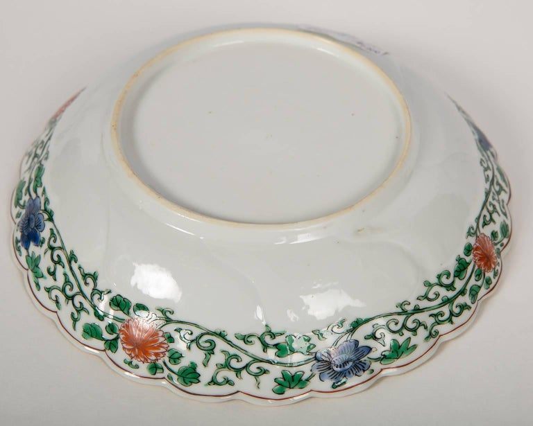 This petite Chinese dish is exquisitely hand-painted in Famille Verte colors of green, blue and red. Dating from circa 1740 it is decorated with floral scenes. The center features a landscape with a pheasant perched on top of a Taihu rock. The