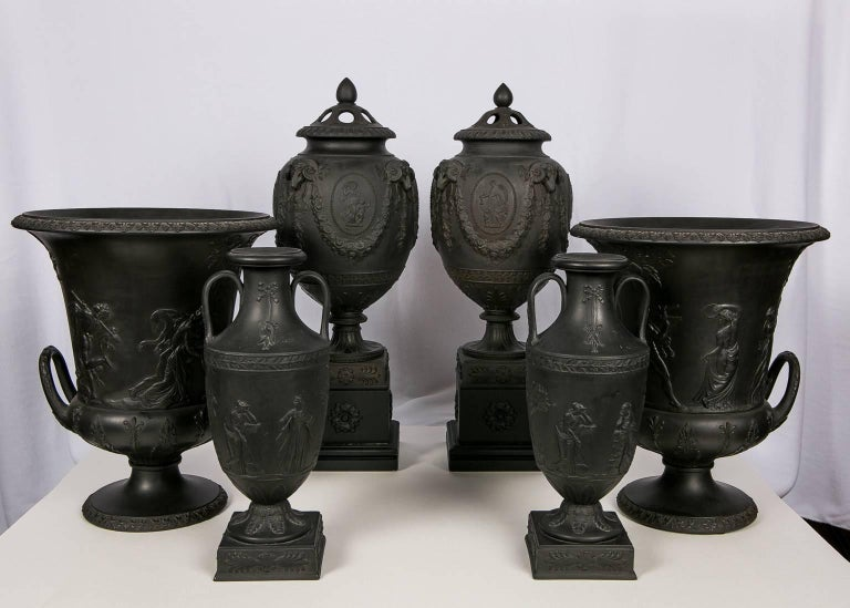 A collection of Wedgwood black basalt vases all decorated with classical figures raised in relief. The group consists of:  The collection consists of a pair of early 19th century covered vases, a pair of early 19th century urns, and a pair of 20th