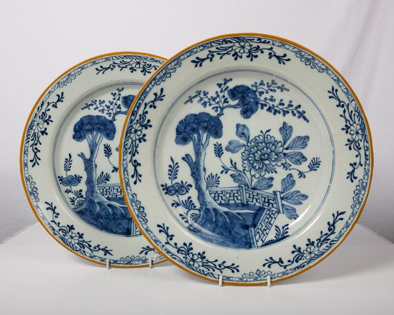 We are pleased to offer this pair of antique Dutch Delft blue and white chargers made in the 18th century, circa 1780. The center is painted in shades of soft cobalt blue showing a garden scene with a deep rooted pine tree, a large peony, and a
