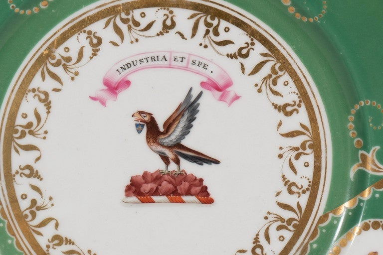 A forest green armorial dish with a crest and motto