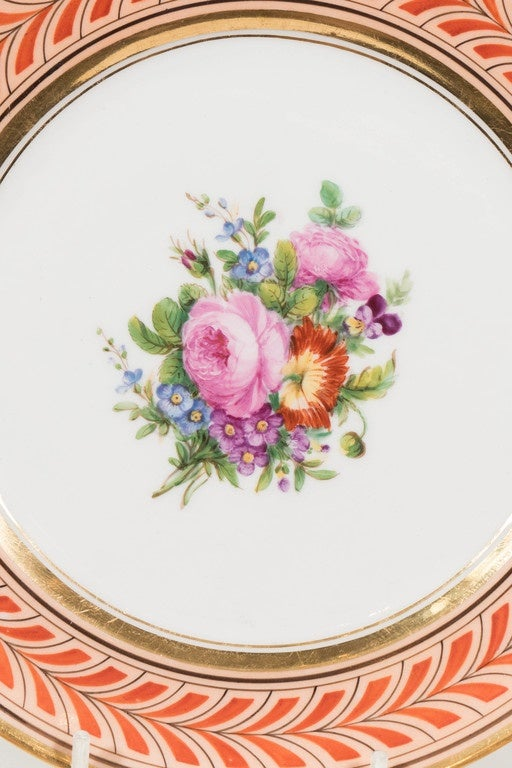 A rare and beautiful set of eleven Edouart Honore, Paris porcelain dishes. These antique French porcelain plates are each hand-painted with a unique bouquet of beautiful flowers. Pinks, greens and light blue play against the border which is painted