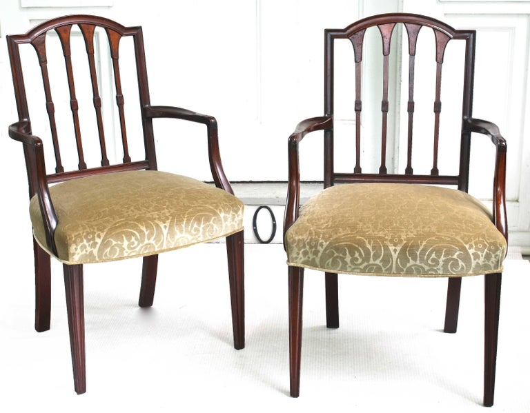 Two solid carved mahogany armchairs and six side chairs. Finely detailed including walnut burl veneers applied to the back-spindle vasiform tops. American Centennial in spirit, believed to be of New England origin. This set of eight chairs may be