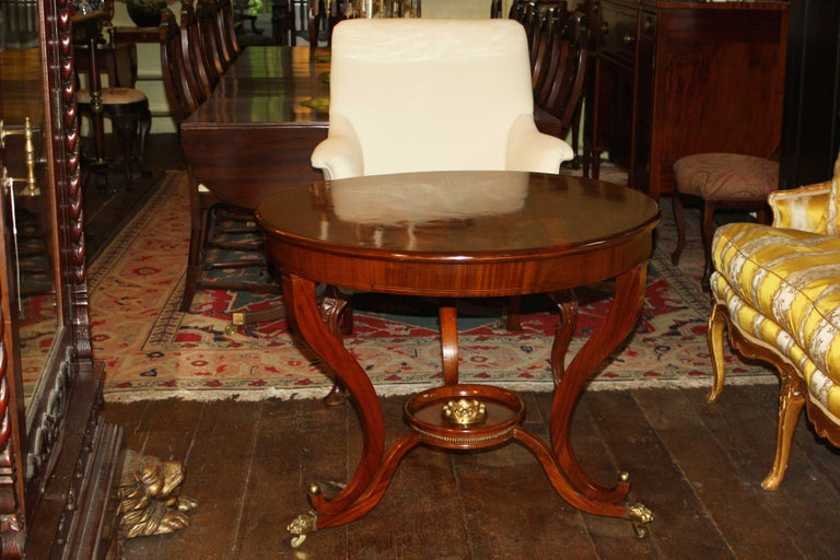German round center table to the neoclassical taste. Mahogany with boxwood string inlays. Brass details include a floral circular mount in the dish stretcher platform, row of brass beading, and ball mounted paw form casters. Related examples: see