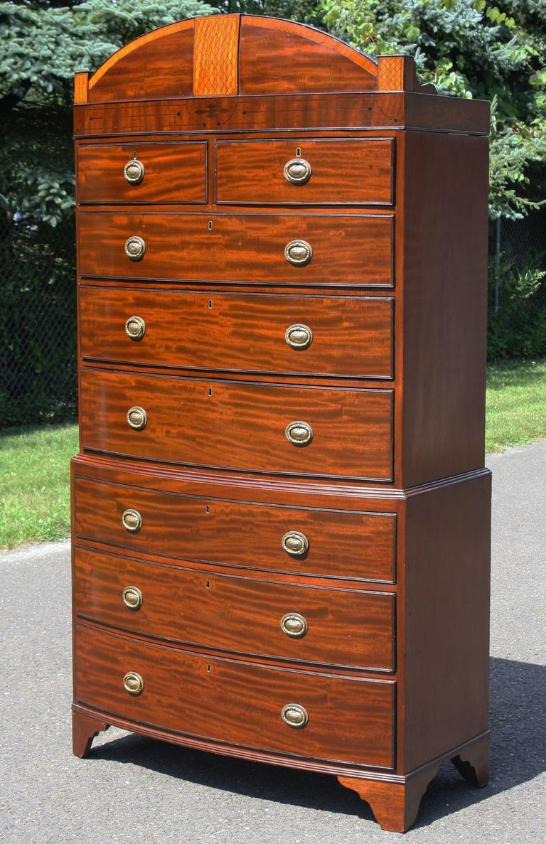 In the Hepplewhite manner, an eight-drawer bowfront chest of strikingly grained mahogany. The domed pediment crown is decorated with sharply contrasting banding, lattice-inlaid center plaque, and corner turret veneer panels. Fine ovoid ring brasses,