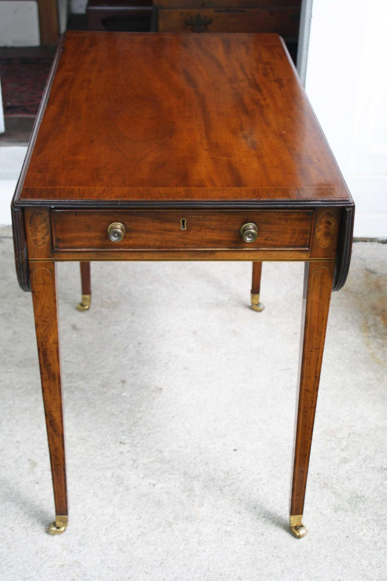 In the Hepplewhite manner, a fine line and ebony inlaid, rosewood banded drop-leaf Pembroke table. Both its functional and faux drawer fronts are beaded and surrounded by elliptical inlays. Brass drawer pulls as well as leg cups and casters appear